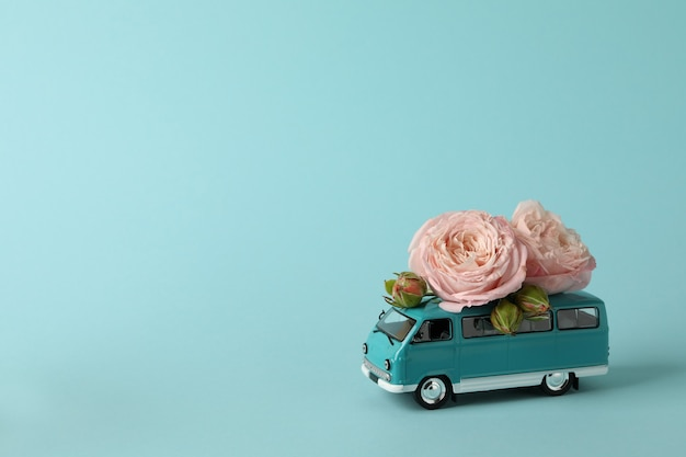 Игрушечный автобус с розовыми розами на синем фоне