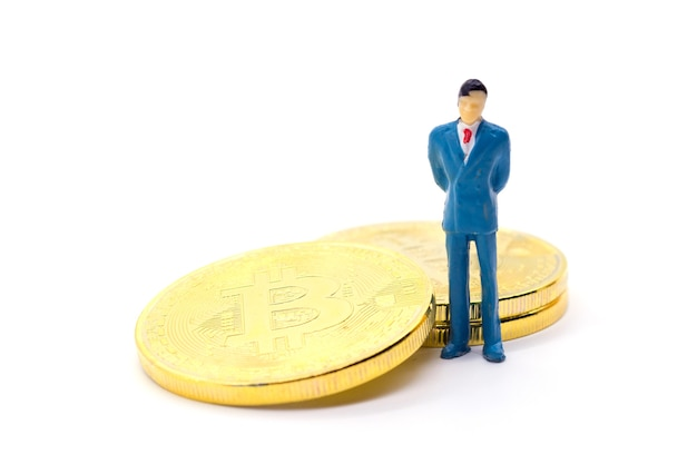 Toy businessman and bitcoin on white background