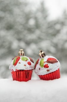 Toy cakes on snow winter holiday background