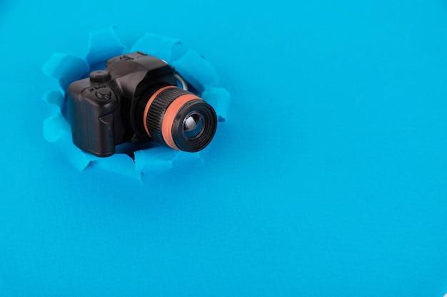 파란색 배경에 장난감 카메라입니다. 개념. 공간 복사