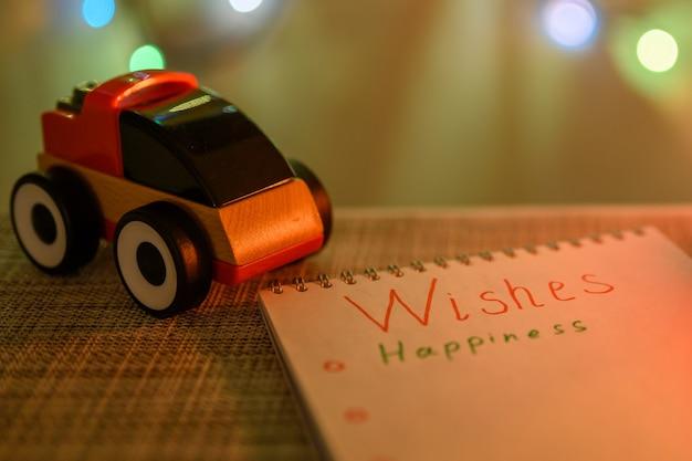 새해 배경과 반짝이는 화환에 있는 아이의 장난감 자동차와 크리스마스 소원.