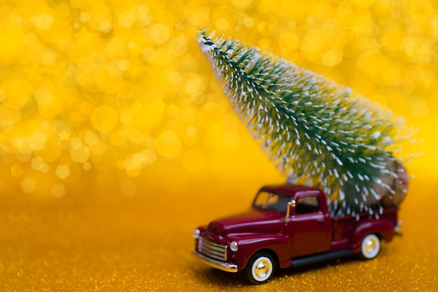 Toy car carries christmas tree for holiday