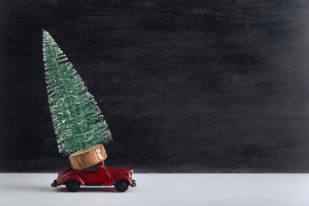 おもちゃの車はミニチュアのクリスマスツリーを運びます。クリスマスツリーのコンセプトの配信。コピースペース