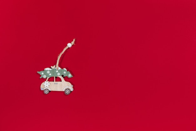 Toy car carrying a handmade hanging christmas tree on a red background