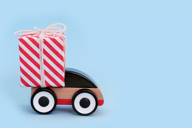 Toy car delivering christmas or new year gift. christmas holiday celebration and new year concept, copy space