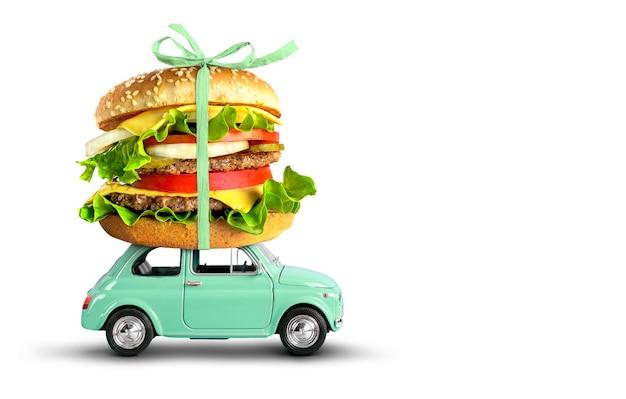 Игрушечный автомобиль, доставляющий гамбургер из фаст-фуда, изолированные на белом фоне