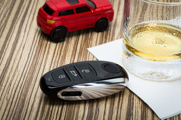 Toy car and glass of whiskey metaphor crash accident isolated