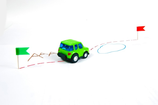 おもちゃの車は白い背景に描かれたルートに沿って進みます
