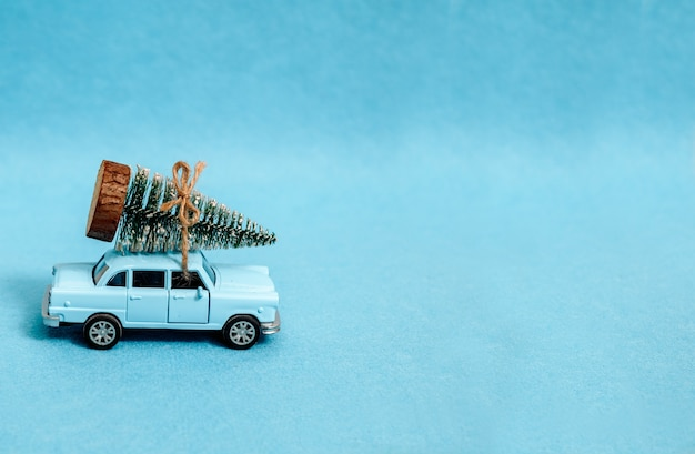 A toy car is driving a christmas tree. on a blue background.
