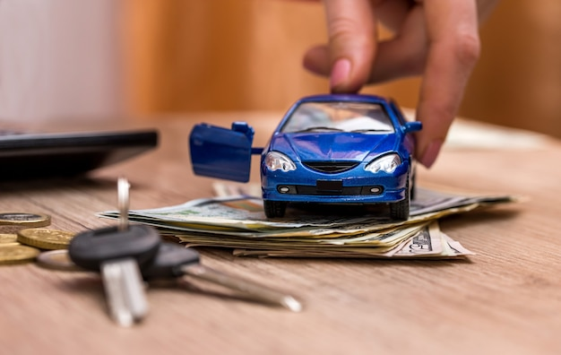 Toy car, keys and money on table