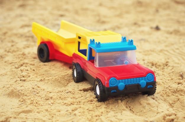 砂の上のおもちゃの車。デザインの要素。