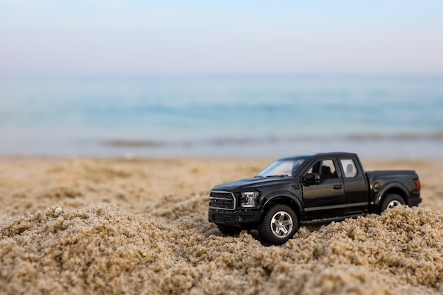 바다를 배경으로 모래 위의 장난감 자동차