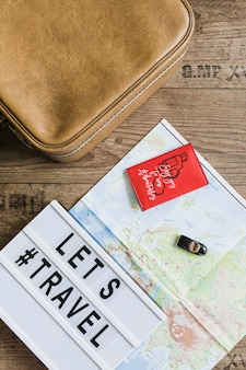 Toy car over the map with lets travel text and bag on wooden table