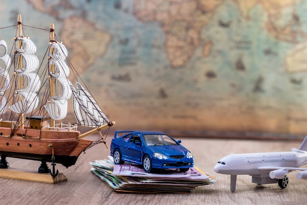 Toy car plane and boat with euro money and map