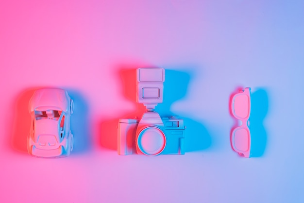 Toy car; retro camera and spectacle arranged in a row on pink backdrop with blue light effect