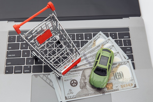 Toy car and shopping cart with money on a laptop. online purchase car concept.