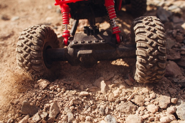 Toy car skidding on dry landscape, close-up.