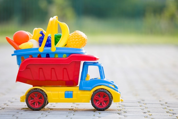 Toy car truck carrying basket with toy fruits and vegetables.