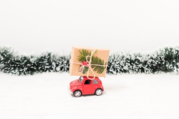 Toy car with gift box near tinsel