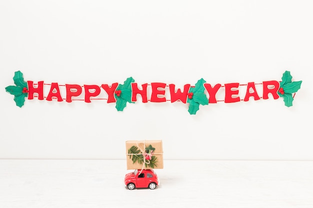 Toy car with gift near happy new year inscription