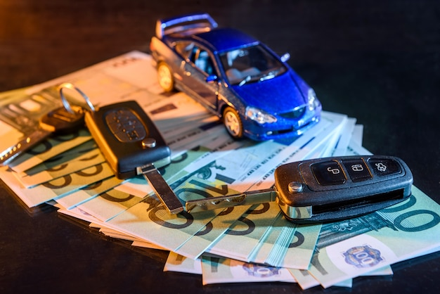 Toy car with keys on euro banknotes at black