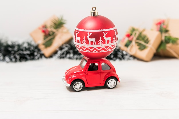 Toy car with red christmas ball near present boxes