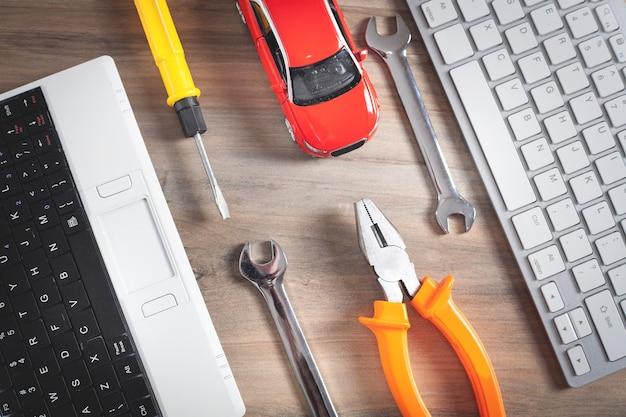 おもちゃの車、レンチ、ドライバー、ペンチ、コンピューターのキーボード。