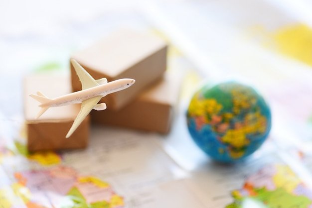 Toy cargo plane and boxes with globe an map