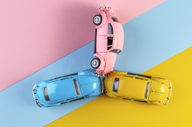 Toy cars in accident on a pastel colorful background. racing cars on the race track.
