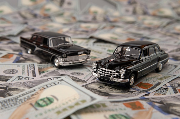 Toy cars on the background of dollar bills
