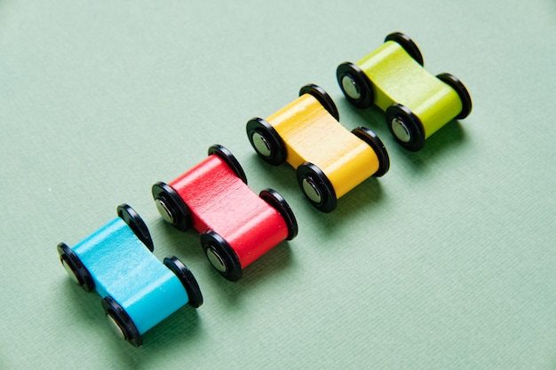 Toy cars made of wood of different colors are stand in a row