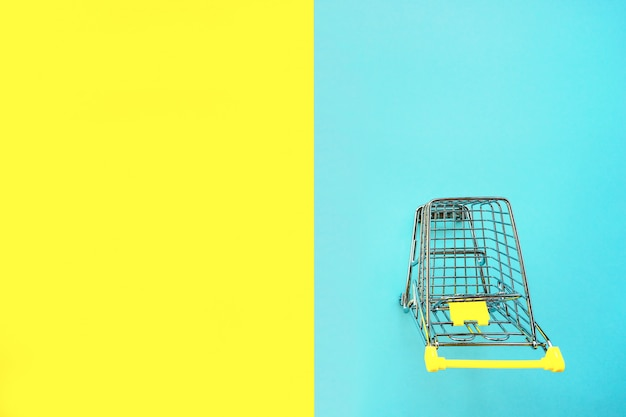 Toy cart for products on a two color yellow blue background.
