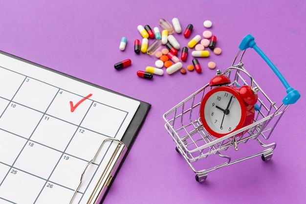 Carrello del giocattolo con orologio e pillole accanto sulla scrivania