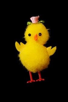 검은 배경에 고립 된 장난감 치킨입니다. 작은 노란색 재미 있는 닭. 고품질 사진