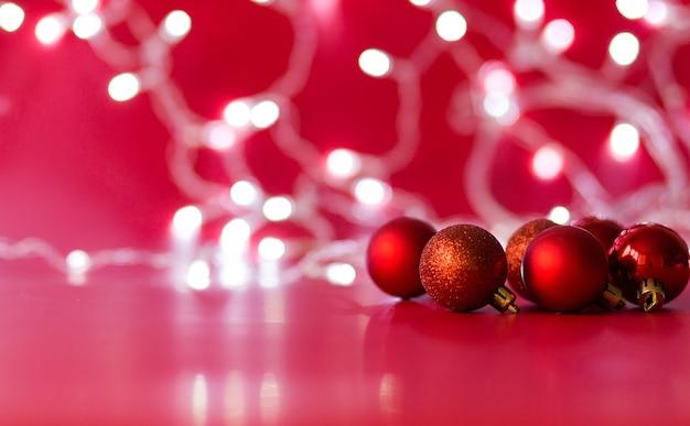 赤い色のおもちゃのクリスマスボールは赤い背景の上にあります