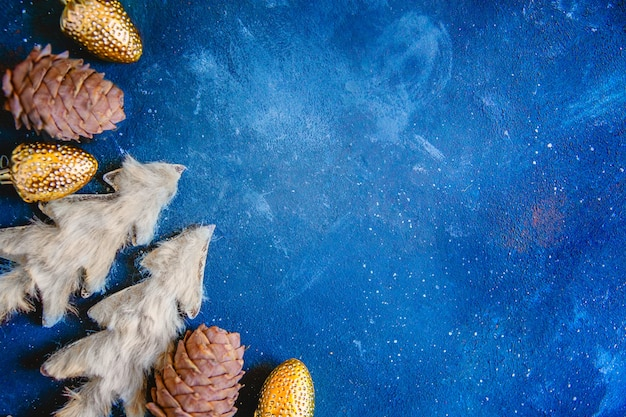 어두운 파란색 그런 지 배경에 전나무와 소나무 콘과 함께 장난감 크리스마스 트리. 텍스트를위한 공간이있는 새해의 평면 레이아웃