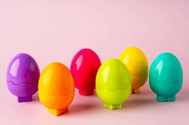분홍색 배경에 장난감 색깔의 플라스틱 달걀. 장난감 밝은 부활절 배경. 몬테소리 부활절 개념입니다. 아이들을 위한 부활절 달걀.