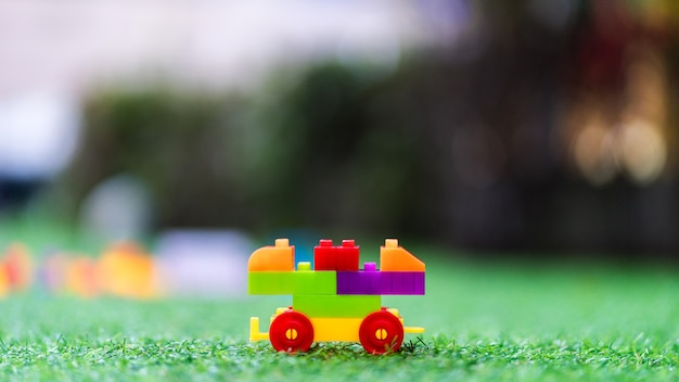 Toy colorful plastic blocks assembled to build a car on playground