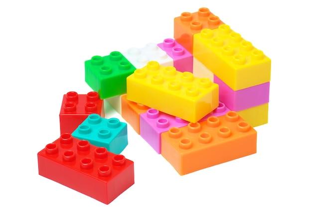 白い背景で隔離のおもちゃのカラフルなプラスチックブロック。カラフルなビルディングブロック