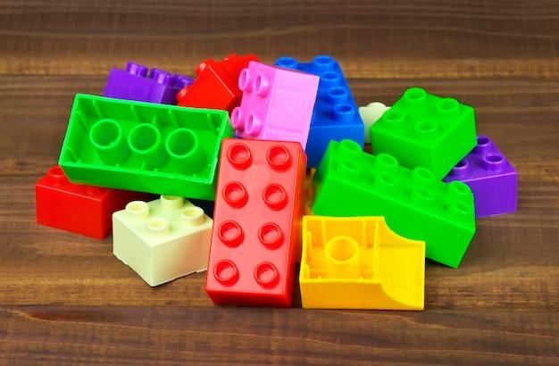 木製の背景に分離されたおもちゃのカラフルなプラスチックブロック