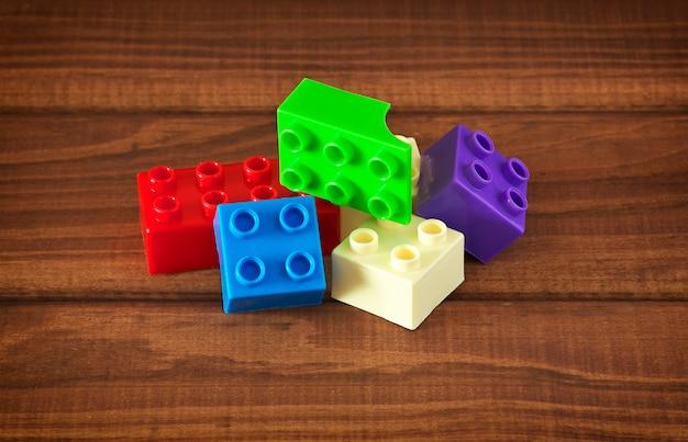 木製の背景にカラフルなプラスチックブロックのおもちゃ