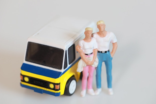 Toy couple man and woman are standing near mini van car for travel on white, isolate figure tourist