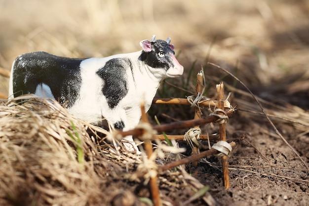 Игрушечная корова сфотографирована на улице с забором из веток на земле в траве