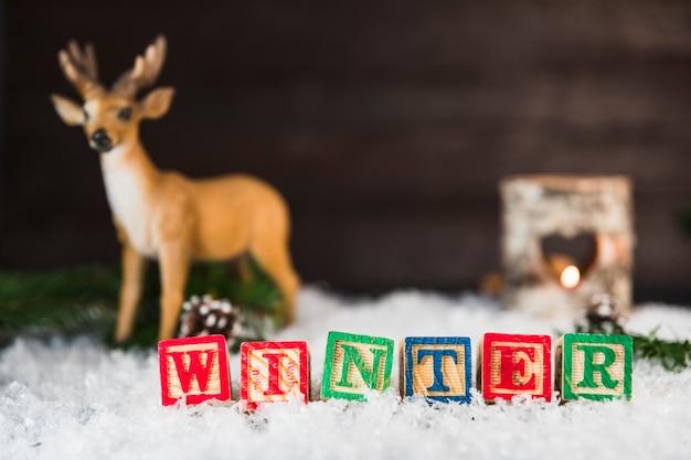 鹿の近くのおもちゃキューブ、雪の上に枝と分岐