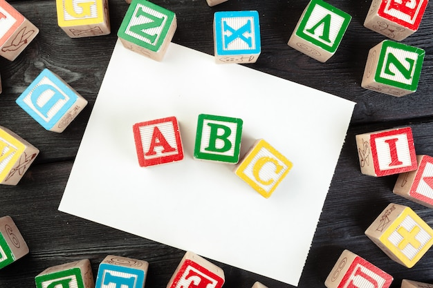 Toy cubes with letters on wooden, copy space