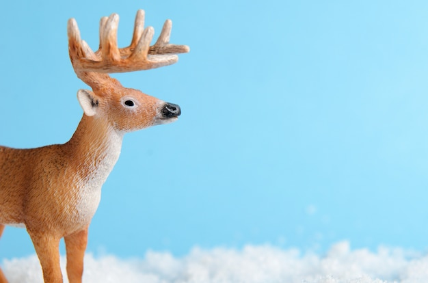 Toy deer on blue standing on artificial snow