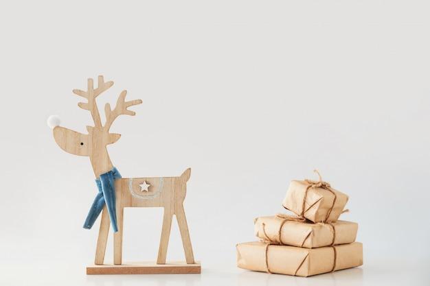 Игрушечный олень несет стопку подарочных коробок. рождество и новогодняя концепция