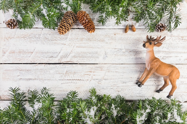 Toy deer and fir twigs on wood board