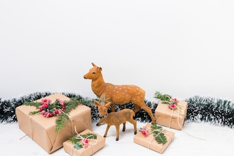 Toy deer near present boxes and tinsel