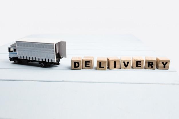 ボックスと青色の背景に木製キューブのおもちゃの配達用トラック